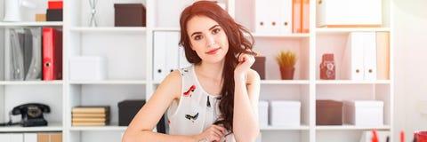 一个美丽的女孩在她的手上坐在办公室桌上,握她的头发并且看得直接 免版税库存图片