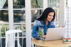 一个美丽的女孩在她的膝上型计算机收到了某一好消息,读它,微笑并且写答复 模型在a坐 库存图片