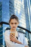 一个美丽的女孩在摩天大楼的背景中拿着一个手机 免版税图库摄影