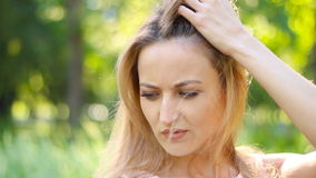 一个美丽的女孩在有被风吹头发的公园摆在 股票视频