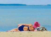 一个美丽的女孩在水库的岸说谎并且看平静的蓝色距离水,报道用抽烟 免版税库存照片