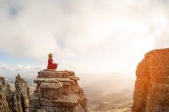 一个美丽的女孩在莲花姿势思考坐在云彩上的一个岩石反对日落的背景 库存图片
