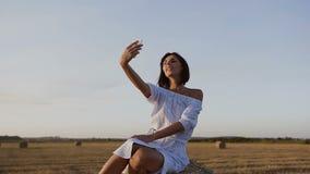 一个美丽的女孩在领域坐干草堆并且使用做selfie的电话 蓝色礼服的可爱的少妇 股票录像