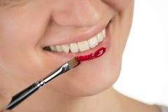 一个美丽的女孩应用一支坚持液体发光的红色唇膏 免版税图库摄影