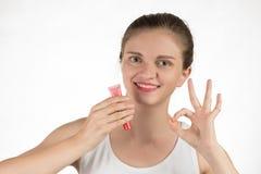 一个美丽的女孩应用一支坚持液体红色唇膏 图库摄影