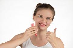 一个美丽的女孩应用一支坚持液体红色唇膏 免版税库存图片