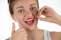 一个美丽的女孩应用一支坚持液体红色唇膏 免版税图库摄影