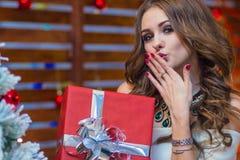 一个美丽的女孩拿着一个红色礼物盒并且送空气亲吻 库存照片