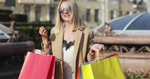 一个美丽的女孩拿着与购买的购物袋在她的手上并且谈话 股票录像