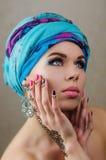 一个美丽的女孩有明亮的构成的,一条蓝色头巾的画象和有在手mihendi的一个样式的 免版税库存图片