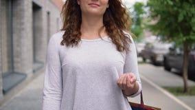 一个美丽的女孩步行沿着向下城市街道在购物以后 4K 画象 股票视频