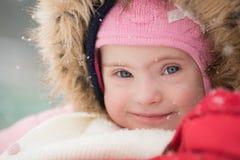 一个美丽的女孩的冬天画象有唐氏综合症的 免版税库存图片
