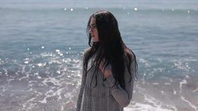 一个美丽的女孩的半身射击有长的黑发的在海边 转动她的头的女孩 振翼的头发  影视素材