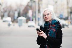 一个美丽的女孩的室外画象秋天的给使用在城市的背景的一个电话的学生穿衣 免版税库存照片
