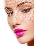 一个美丽的女孩的时尚画象头戴在眼睛的面纱 照亮 免版税库存图片