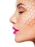 一个美丽的女孩的时尚画象头戴在眼睛的面纱 照亮 免版税图库摄影
