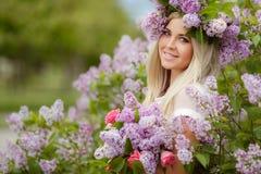 一个美丽的女孩的春天画象有丁香的 库存照片
