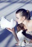 一个美丽的女孩的柔和的画象有一只白色鸠的,在s 免版税库存照片