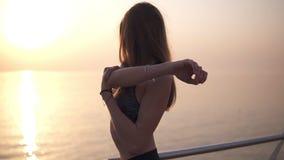 一个美丽的女孩的特写镜头体育胸罩的舒展她的胳膊肌肉 白肤金发头发长 太阳是光亮的 股票录像