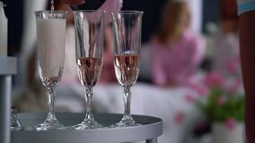 一个美丽的女孩的特写镜头用获得乐趣在背景在a的女朋友的香槟玻璃填装 影视素材