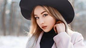 一个美丽的女孩的特写镜头画象一个时髦的帽子的在wint 免版税库存图片