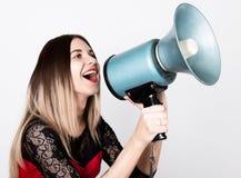 一个美丽的女孩的特写镜头画象一件红色礼服的有鞋带袖子的,她叫喊入手提式扬声机 公共关系 免版税库存照片