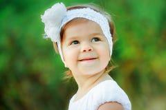 一个美丽的女孩的画象一个白色鞋带头饰带的有一朵大花的 库存照片