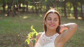 一个美丽的女孩的画象一件夏天礼服的在一个晴朗的绿色公园 影视素材