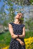 一个美丽的女孩的画象一件蓝色礼服的在有blosoming的苹果树的庭院里有乐趣和享用 库存照片