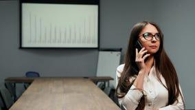 一个美丽的女孩的画象在办公室在有玻璃的一间会议室给身分穿衣谈话在一个手机  影视素材