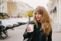 一个美丽的女孩的画象在城市街道上的,在她的手上拿着一纸杯 免版税库存照片