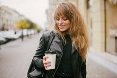 一个美丽的女孩的画象在街道上的,拿着一纸杯 免版税库存照片