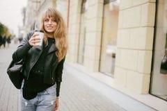 一个美丽的女孩的画象在街道上的,拿着一纸杯 库存图片