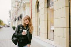 一个美丽的女孩的画象在街道上的,拿着一纸杯 图库摄影
