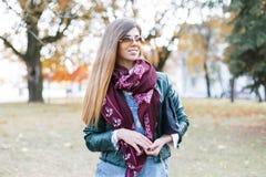 一个美丽的女孩的画象太阳镜、围巾和夹克的 图库摄影