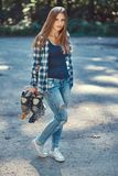 一个美丽的女孩的画象有长的头发佩带的羊毛衬衣和牛仔裤的,举行路辗 图库摄影