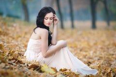 一个美丽的女孩的秋天画象桃红色礼服的 库存图片