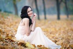 一个美丽的女孩的秋天画象桃红色礼服的 免版税库存照片