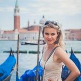一个美丽的女孩的纵向前Venezian运河长平底船的 库存图片