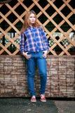 一个美丽的女孩的纵向 微笑,摆在照相机 在笼子的一件蓝色衬衣 在背景木栅格栅格 免版税库存图片