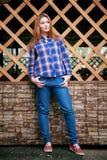 一个美丽的女孩的纵向 微笑,摆在照相机 在笼子的一件蓝色衬衣 在背景木栅格栅格 库存照片