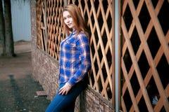 一个美丽的女孩的纵向 微笑,摆在照相机 在笼子的一件蓝色衬衣 在背景木栅格栅格 免版税图库摄影
