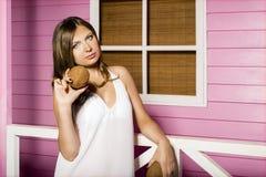 一个美丽的女孩的纵向 性感的妇女在海滩桃红色房子附近在她的手上站立并且拿着椰子 免版税图库摄影