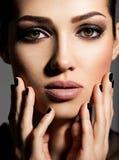 一个美丽的女孩的面孔有时尚构成和黑钉子的 免版税库存照片