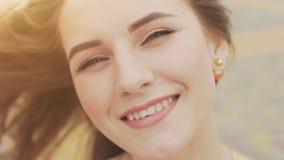 一个美丽的女孩的面孔有深蓝眼睛特写镜头的 在面孔整洁的天构成 查找肉欲 在风的头发 股票视频