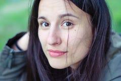 一个美丽的女孩的面孔没有构成的与黑眼睛和头发有雀斑的 免版税库存图片