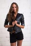 一个美丽的女孩的画象一件黑夹克和短裤的 白色砖墙,没被隔绝 免版税库存图片