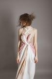 一个美丽的女孩的画象一件浅粉红色的礼服的在灰色背景、健康的概念和秀丽的演播室 免版税库存照片
