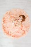 一个美丽的女孩的画象一件米黄桃子礼服的 免版税库存图片