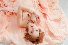 一个美丽的女孩的画象一件米黄桃子礼服的 库存图片